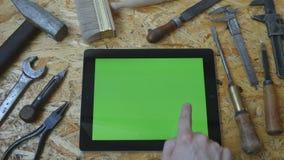 Main masculine de l'artisan d'artisan à l'aide du PC de comprimé avec l'écran vert dans l'atelier Vue supérieure Mensonge différe banque de vidéos