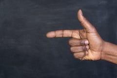 Main masculine dirigeant un doigt sur un tableau noir Photo stock