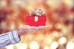 Main masculine donnant un boîte-cadeau Photos stock