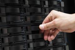 Main masculine du ` s de technicien remplaçant l'unité de disque dur en San photos libres de droits