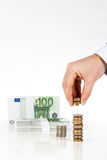 Main masculine empilant des pièces de monnaie avec d'euro billets de banque sur le fond Photo libre de droits