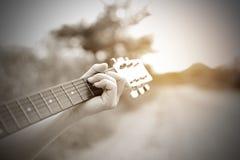 Main masculine en gros plan jouant sur la guitare acoustique extérieure avec la lumière du soleil Ton de vintage images stock