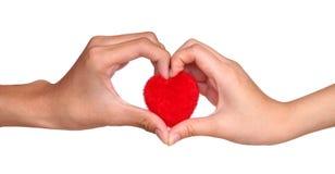 Main masculine et femelle de signe jugeant un coeur rouge d'isolement sur le blanc Images stock