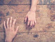 Main masculine et femelle sur la table en bois Photo libre de droits