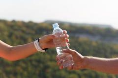 Main masculine et femelle tenant la bouteille d'eau sur le fond de nature Images stock