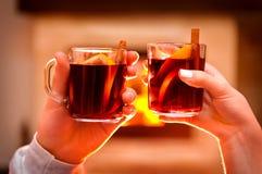Main masculine et femelle tenant une tasse de vin chaud Photographie stock libre de droits