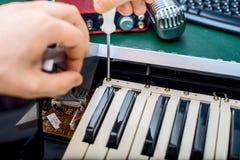 Main masculine fixant le clavier du Midi Photos libres de droits