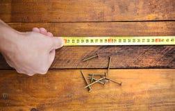 Main masculine mesurant le plancher en bois Photographie stock