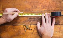 Main masculine mesurant le plancher en bois Image stock