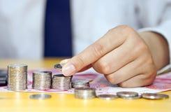 Main masculine mettant des pièces de monnaie en colonnes Photos libres de droits