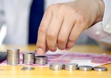 Main masculine mettant des pièces de monnaie en colonnes Photographie stock