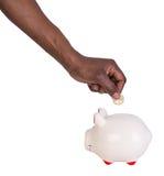 Main masculine mettant une pièce de monnaie dans une tirelire Images stock