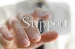 Main masculine se dirigeant à l'icône de soutien sur un écran virtuel photos stock