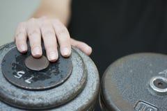 Main masculine sur le poids d'haltère Photographie stock libre de droits