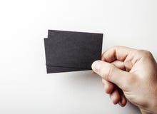 Main masculine tenant deux cartes de visite professionnelle de visite noires sur image stock