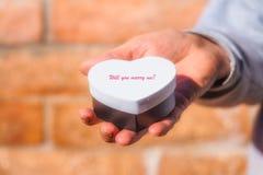 Main masculine tenant le boîte-cadeau en forme de coeur Image stock