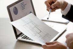 Main masculine tenant le plan de projet, statistiques sur l'écran, fin  Image stock