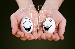La main masculine tenant se tenir eggs avec les visages souriants Photo stock