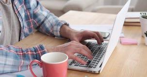 Main masculine travaillant à l'ordinateur portable et au bureau potable de café à la maison clips vidéos