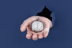 Main masculine traversant le fond de papier bleu et tenant l'horloge antique Photo libre de droits