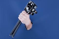 Main masculine traversant le fond de papier bleu et tenant le rétro appareil-photo Photographie stock