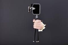 Main masculine traversant le fond de papier noir et tenant le rétro appareil-photo Photo libre de droits