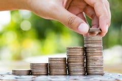Main mettant des pièces de monnaie pour inventer le graphique croissant de pile images libres de droits