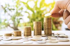 Main mettant l'élevage de pile de pièces de monnaie d'argent Photo stock