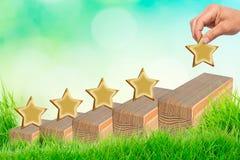 Main mettant la forme en bois de cinq étoiles sur la table Les meilleurs excellents services aux entreprises évaluant le concept  photo stock