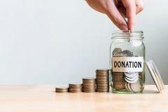 Main mettant la pièce de monnaie dans la donation de mot de pot avec la pile d'argent, concept Images libres de droits