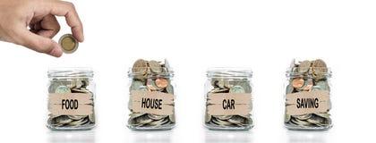 Main mettant la pièce de monnaie dans le pot en verre Affectez l'argent pour les nourritures, la maison, la voiture et l'épargne  photo stock