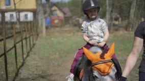 Main mignonne heureuse de vague d'enfant de fille tandis que cheval de poney de licorne de tour Mouvement de cardan banque de vidéos