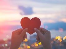 Main molle de foyer tenant le beau coeur pendant le fond de coucher du soleil Photographie stock