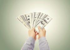 Main montrant une diffusion d'argent liquide Image stock