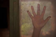 Main mystérieuse sur une fenêtre Images libres de droits