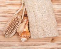 Main naturelle de poil et brosse de clou, éponge de luffa et coquille en bois photos stock
