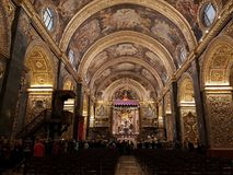 The main nave in the St John Co Cathedral, Valletta, Malta. The main nave with arched ceiling painted by Mattia Preti and gilded columns and marble floor inside royalty free stock image