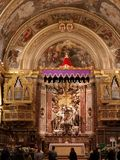 The main nave altar and ceiling in the St John Co Cathedral, Valletta, Malta. The main nave with arched ceiling painted by Mattia Preti and gilded columns and stock images