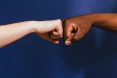 Main noire et blanche, geste de bosse de poing, contraste image libre de droits