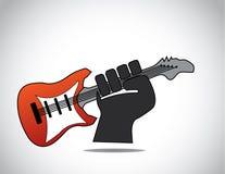 Main noire foncée tenant la guitare rouge lumineuse Photographie stock libre de droits