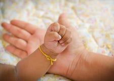 Main nouveau-née de bébé dans la paume de la maman Photographie stock