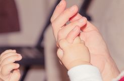 Main nouveau-née de bébé tenant le doigt adulte, concept de maternité Photographie stock libre de droits