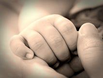 Main nouveau-née de bébé tenant le doigt de mère Photographie stock