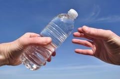 Main offrant une bouteille de l'eau photographie stock