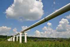 The main oil pipeline of a high pressure. In a summer landscape under clouds royalty free stock photography