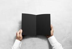 Main ouvrant la maquette noire vide de livret de brochure Images libres de droits