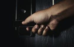 Main ouvrant la porte dans l'obscurité Photographie stock