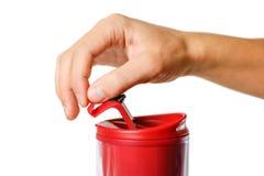 Main ouvrant une tasse thermo rouge Fin vers le haut D'isolement sur le fond blanc image libre de droits
