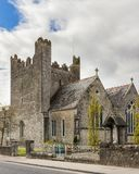 Holy Trinity Abbey Church. The main parish church in Adare, Co. Limerick. Taken on a sunny day. The church is surrounded by a stone wall and iron gate . A statue Stock Photography