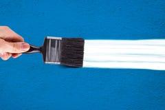 Main peignant le mur bleu Image stock